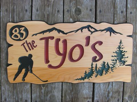 Custom wood sign with hockey player, mountains and trees