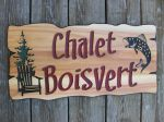 Wood carved sign with chair and trees