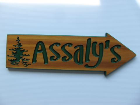 Wooden engraved directional arrows for a cottage with a graphic of a tree